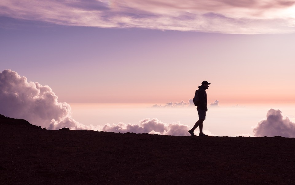 A silhouette of a man walking across a mountain