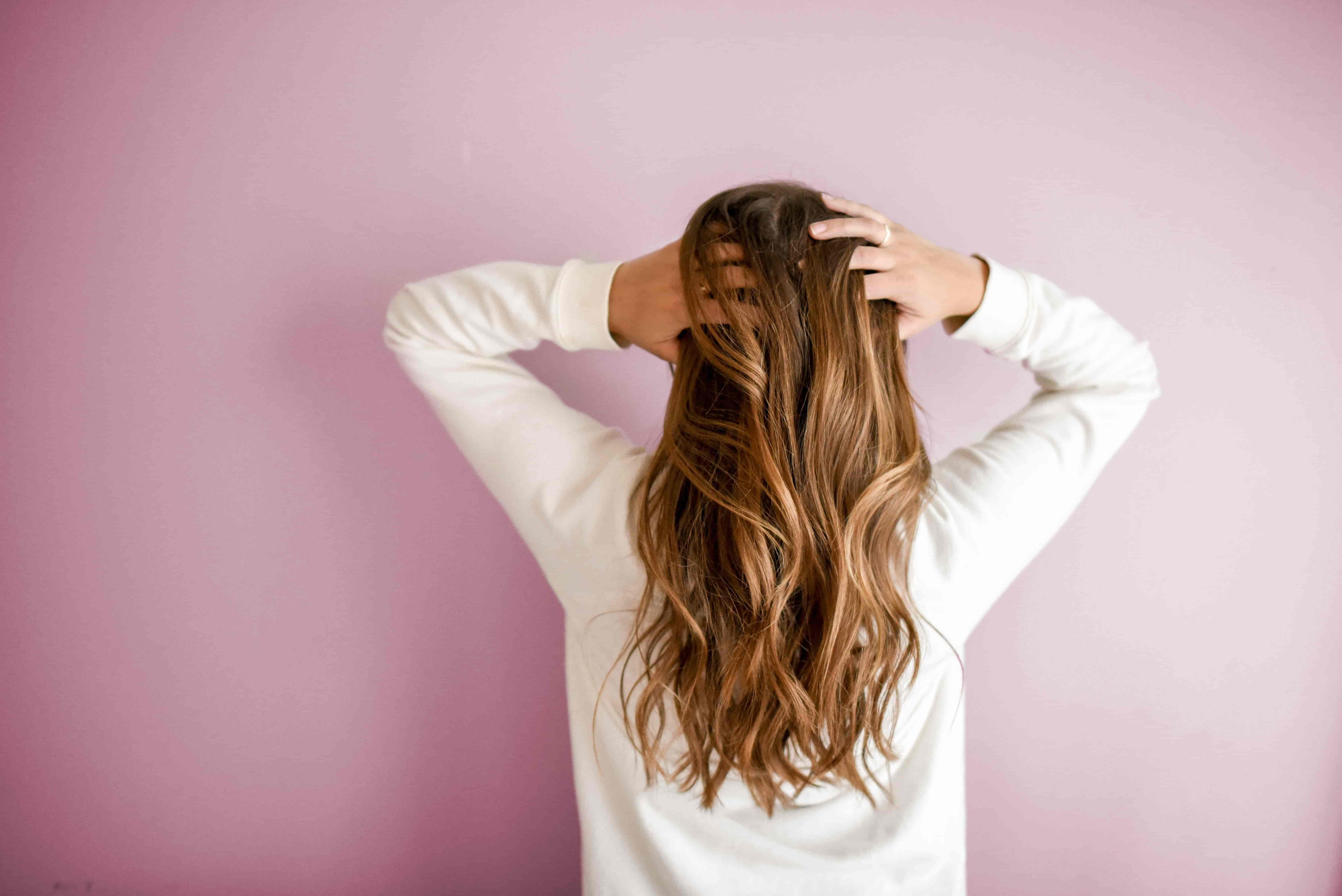 A woman in a cream jumper with long wavy brown hair, with her back towards the camera with both hands on her head on a pink background