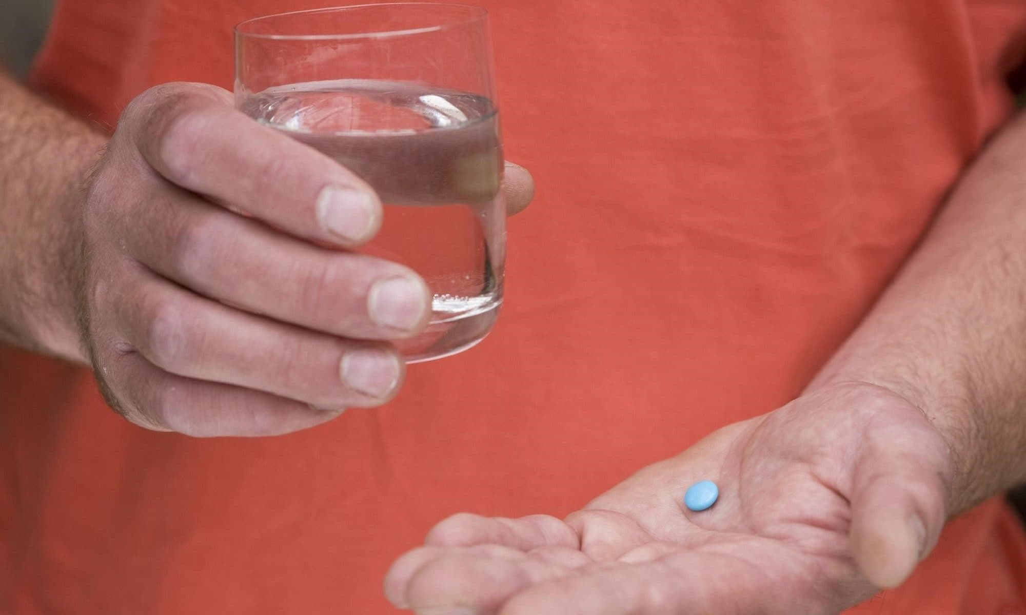 A man holding a glass of water in one hand, and a viagra pill in the other hand